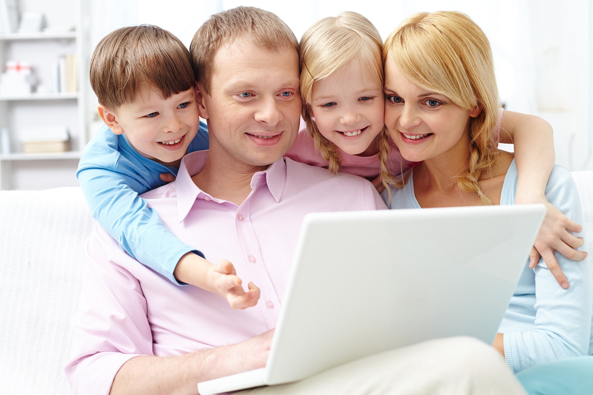 A young family of four using laptop at home